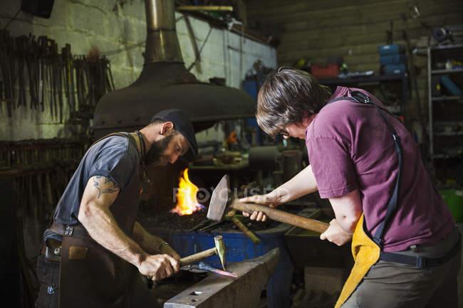 Два ковалі куванням шматок металу на ковадлі в майстерні. — стокове фото
