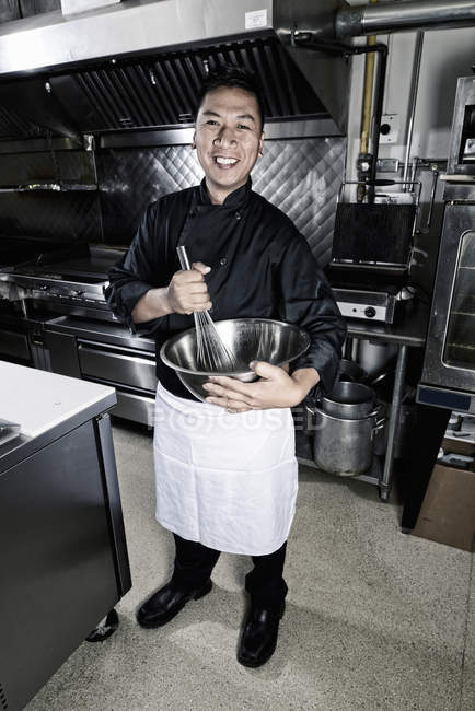 Male cook stirring in mixing bowl in commercial restaurant kitchen. — Stock Photo