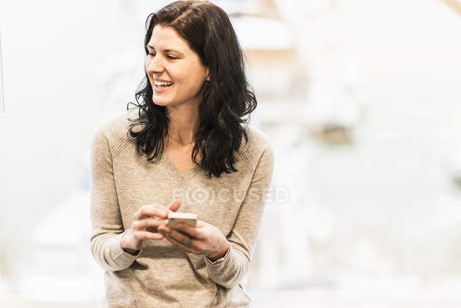 Business woman sitting by window, holding smartphone and laughing. — Stock Photo