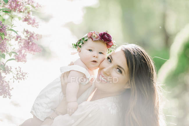 Femme adulte moyenne posant avec bébé fille avec couronne de fleurs à l'extérieur . — Photo de stock
