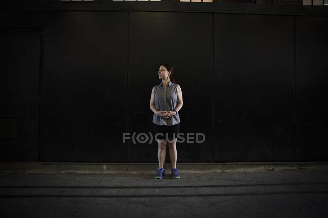 Woman in sleeveless shirt and shorts with running shoes standing in shadow by building on street. — Stock Photo