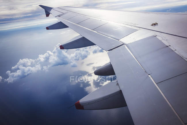 Ala de avión en vuelo contra el cielo azul con nubes . - foto de stock