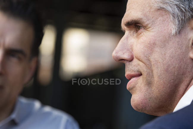 Close-up of men on street looking away. — Stock Photo
