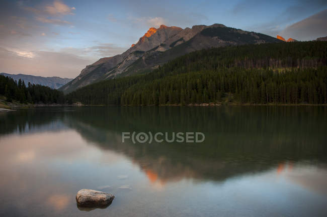 Aguas tranquilas del lago y las montañas de montañas rocosas de Canadá al atardecer - foto de stock