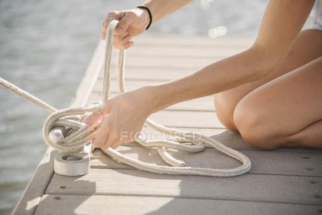 Nahaufnahme der jungen Frau kniend auf Steg und Seil binden — Stockfoto