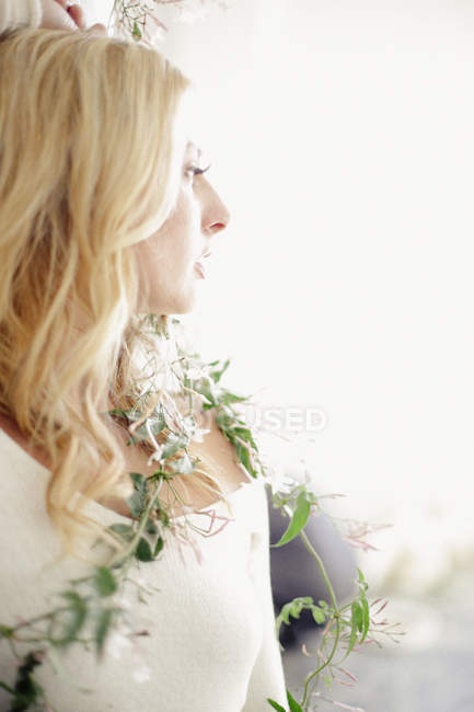 Head and shoulders portrait of blonde woman with wrapped creeper plant. — Stock Photo