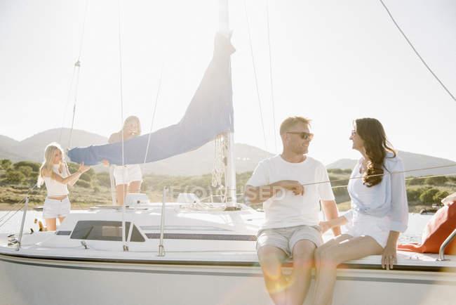 Мужчина и женщина, сидя на яхте с девочек-подростков, работающих в фоновом режиме — стоковое фото