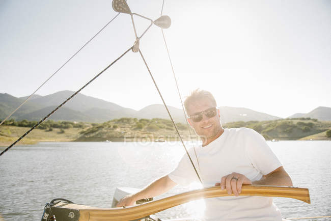 Mature man with sunglasses steering sailboat on lake. — Stock Photo