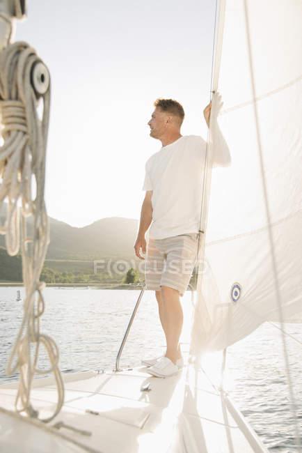 Зрелый человек стоя на яхте и проведение на парус на озере. — стоковое фото