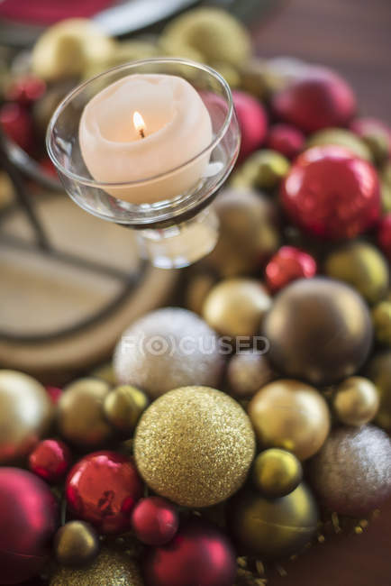 Close-up of colorful Christmas ornaments and candle in candle holder on table. — Stock Photo