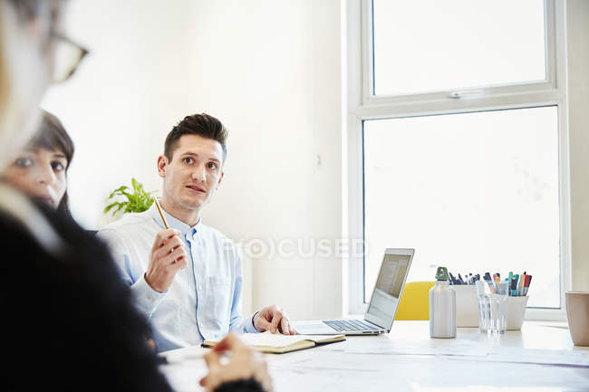 Man using laptop while sitting at table and talking to colleagues in office. — Stock Photo