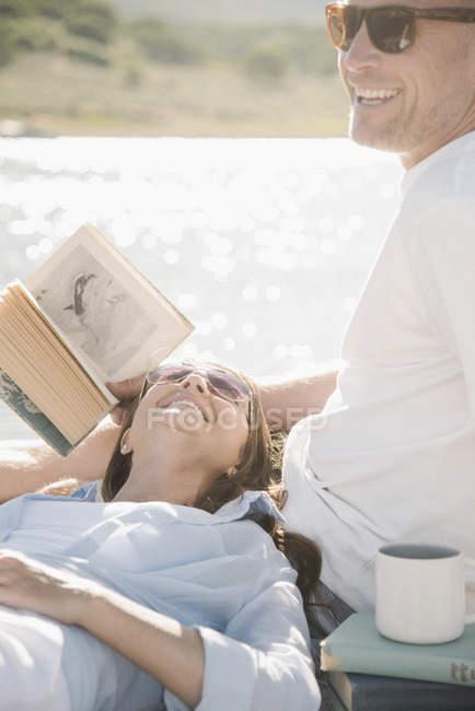 Женщина на колени лежащего человека с книгой на причал. — стоковое фото