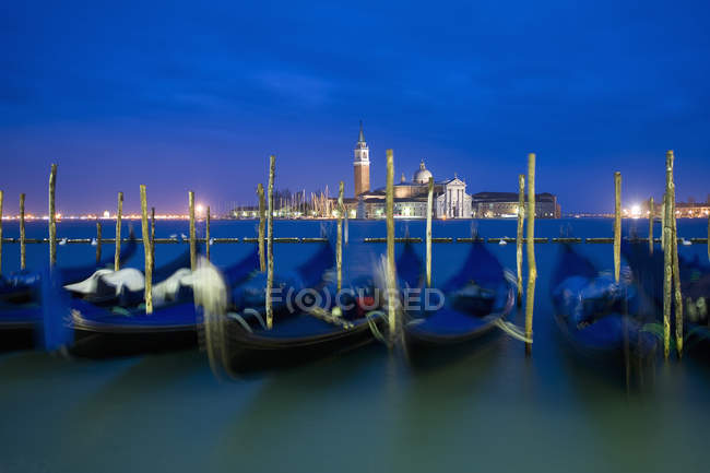 Gondole ormeggiate a riva con vista sull'isola e sulla chiesa di San Giorgio Maggiore al tramonto, Venezia . — Foto stock