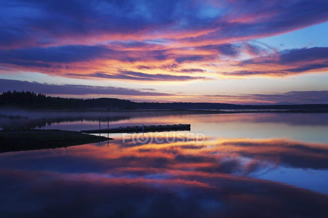 Wooden dock on calm lake at sunset with dramatic cloudscape. — Stock Photo