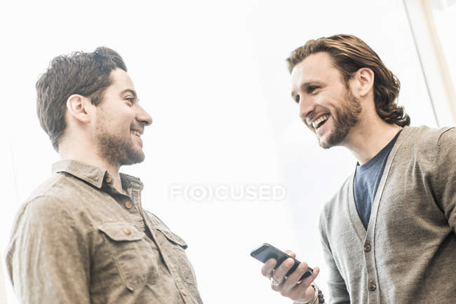 Dos hombres de negocios sonriendo y sosteniendo el teléfono inteligente en la oficina . - foto de stock