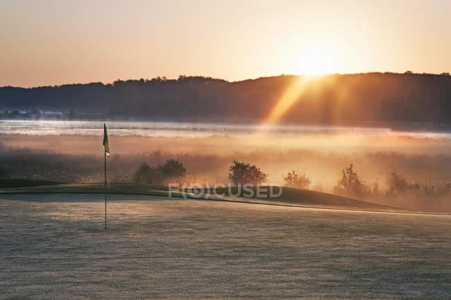 Светящийся рассвета солнечного света на гольф-поле с полюс. — стоковое фото