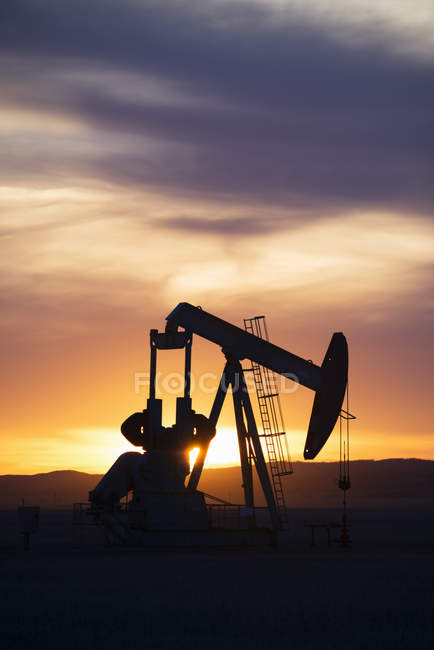 Working pumpjack at oil drilling site at sunset in Canada. — Stock Photo