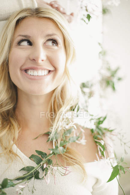 Blonde woman smiling with leafy garland around shoulders. — Stock Photo