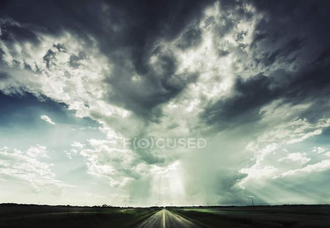 Straße in Richtung Horizont unter dramatischen Himmel erreichen — Stockfoto