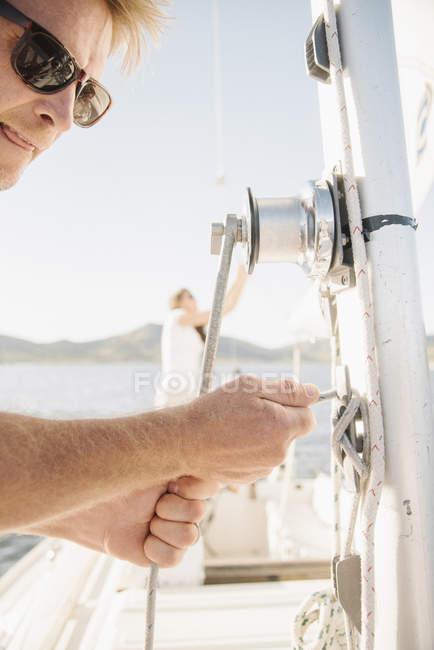 Крупным планом, зрелые мужчины с солнцезащитные очки, привязав веревки на яхте. — стоковое фото