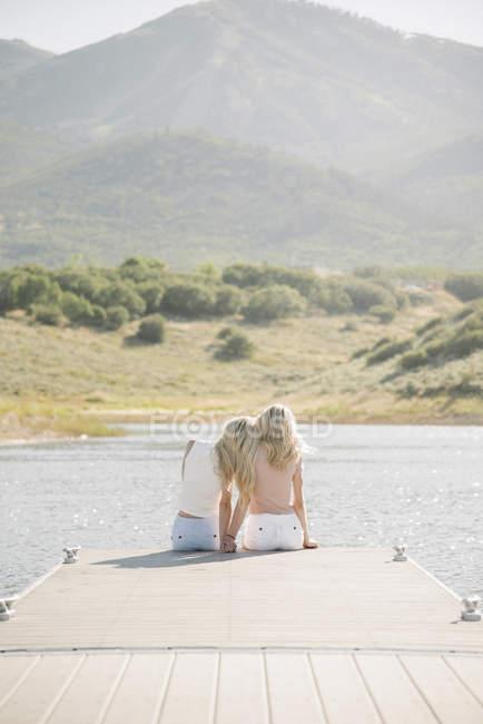 Vista posteriore di due ragazze bionde sedute sul molo del lago . — Foto stock