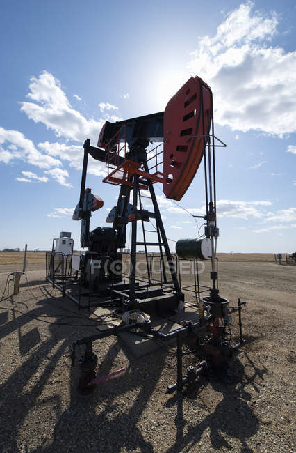 Pump jack in open ground at oil extraction site. — Stock Photo