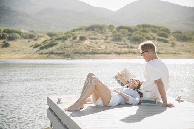 Mann und Frau liegend auf Steg und Lesebuch. — Stockfoto