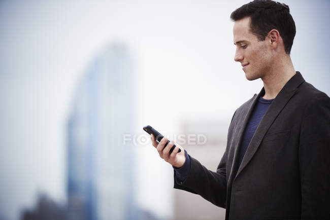 Young businessman standing on rooftop and looking down at smartphone. — Stock Photo