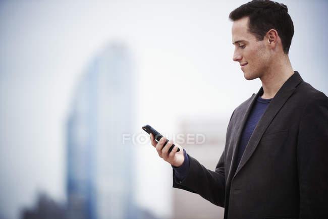 Giovane uomo d'affari in piedi sul tetto e guardando smartphone — Foto stock