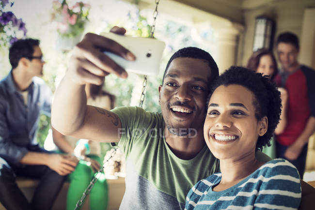 Couple taking selfie with group of friends at house party. — Stock Photo