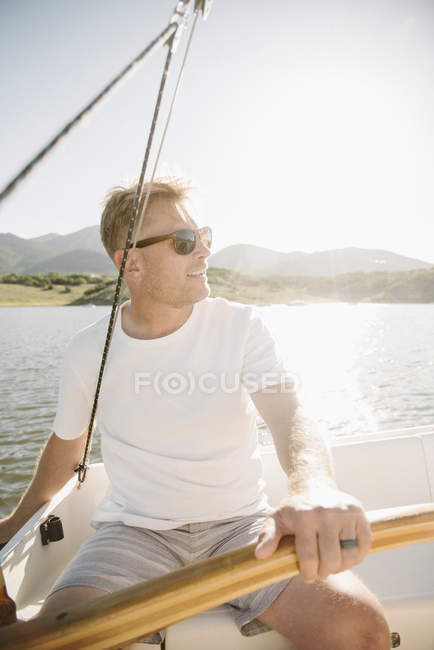 Mature man in sunglasses relaxing and steering sailboat on lake. — Stock Photo