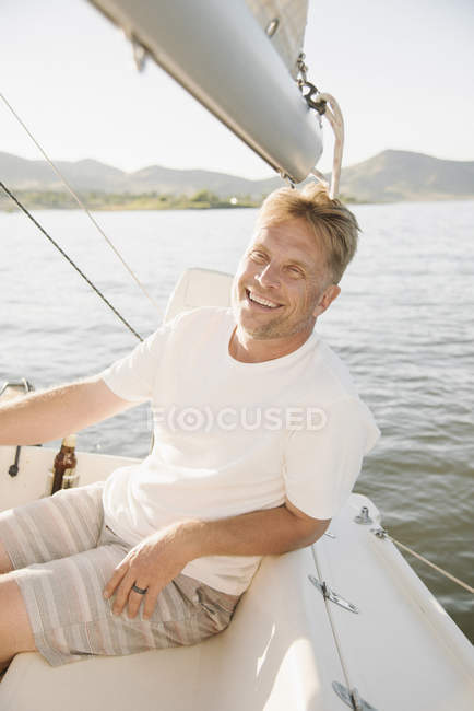 Портрет зрелый человек, расслабляющий на парусная лодка на озере. — стоковое фото