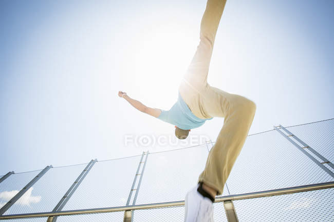 Young man somersaulting on city bridge, low angle view. — Stock Photo