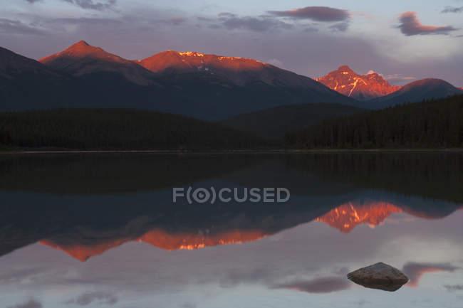 Montagnes Rocheuses canadiennes avec la lumière du soleil reflétant dans l'eau du lac — Photo de stock
