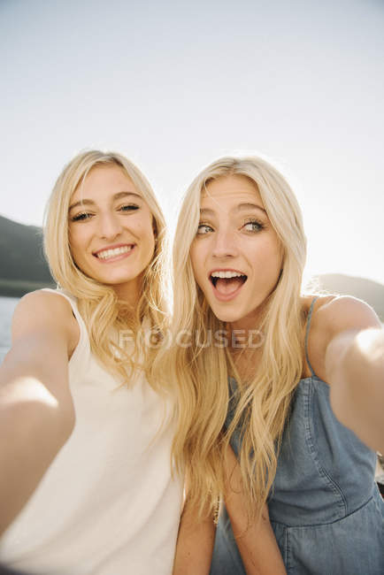 Portrait of two teenage sisters on posing at lake shore. — Stock Photo
