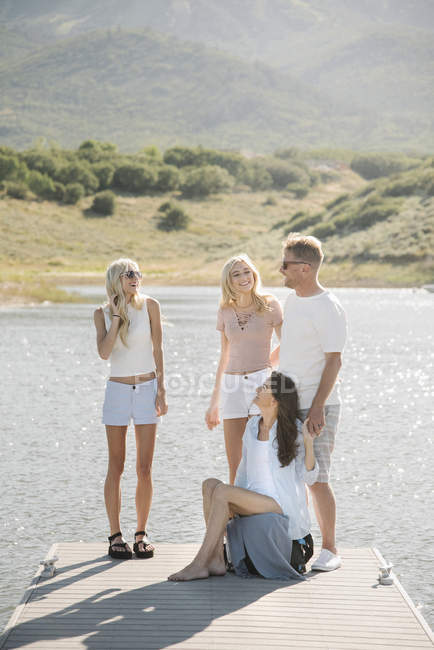 Mature parents with teenage daughters relaxing on lake jetty. — Stock Photo