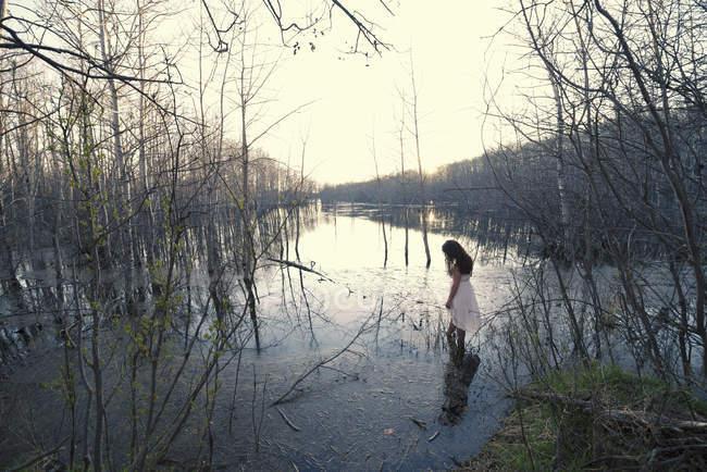 Mulher de vestido branco vadear em águas rasas ao entardecer . — Fotografia de Stock