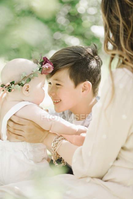 Femme et préadolescent garçon saluant bébé fille en plein air . — Photo de stock