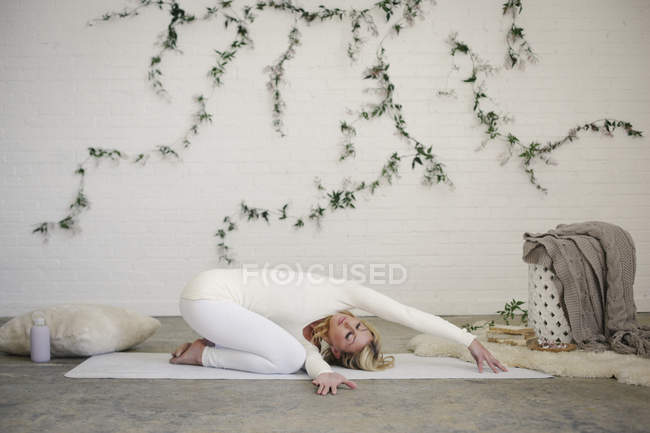 Blonde woman kneeling and twisting on yoga mat with arms outstretched. — Stock Photo