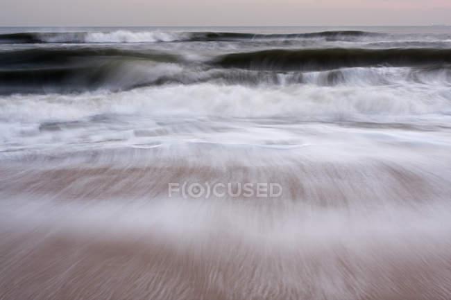 Vagues s'écrasant sur la plage de sable en mouvement flou . — Photo de stock