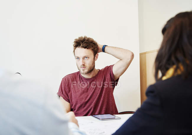 Young man sitting in meeting with colleagues at table. — Stock Photo