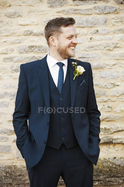 Groom in suit with flower in buttonhole and hands in pockets smiling outdoors. — Stock Photo