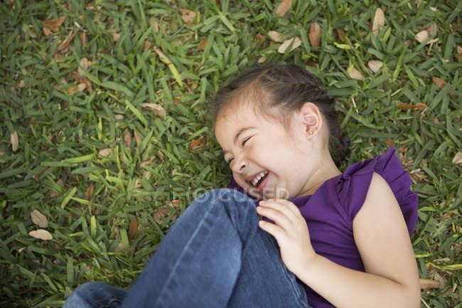 Крупный план девушки, лежащей, обнимающей колени и смеющейся на зеленой траве . — стоковое фото