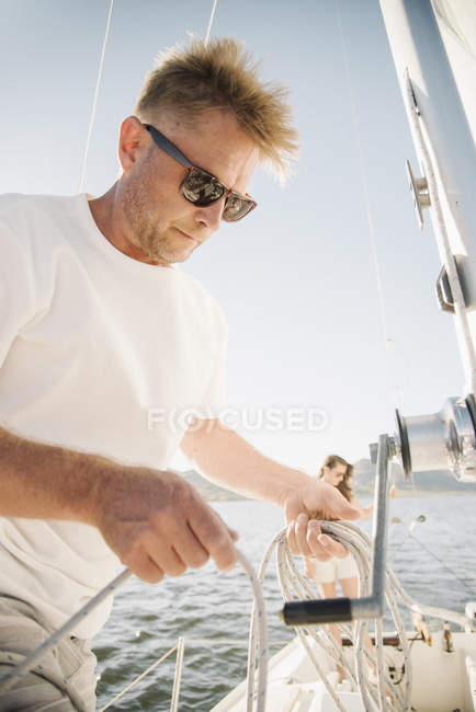Портрет блондинка с солнцезащитные очки, проведение веревки на яхте. — стоковое фото