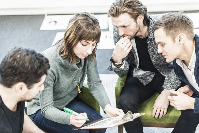 Colleagues at meeting writing with pen on clipboard. — Stock Photo