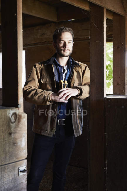 Young man in working clothes standing in barn and holding protective gloves. — Stock Photo