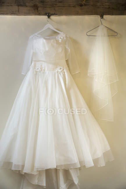 Long white wedding dress with skirt, petticoats and veil on hangers. — Stock Photo