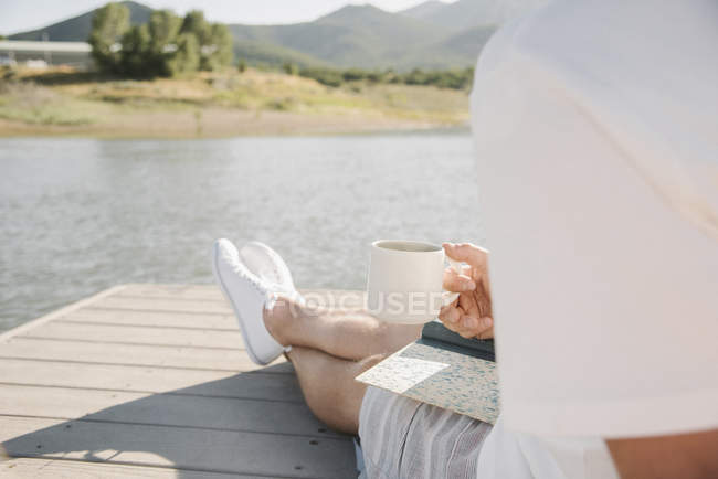 Man sitting on jetty and holding mug and book at lake. — Stock Photo