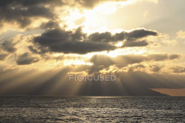 Вали сонячного світла крізь хмари, падаючи на океан води — стокове фото
