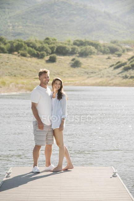 Мужчина и женщина, стоя бок о бок на пристани озера. — стоковое фото